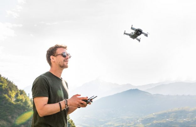male flying drone on hazy day in teh hills